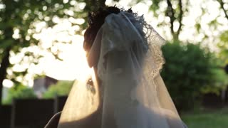 Beautiful bride in a wedding dress, with expensive jewelry and crown, in a elegant bridal vail running in the garden towards the bright sunshine, then turns to camera and smiles. Wedding atmosphere.