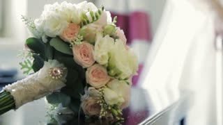 Charming wedding bouquet with glancing diamond lying on the table, then bride in white wedding dress comes up and takes it. Wedding celebration. Accessories of bride, pink roses, sweet bay.