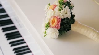 Colorful wedding bouquet on a white piano. Accessories of bride, pink roses, sweet bay, magnolia. No people around. Inside shooting. Wedding atmosphere. Camera stabilizer shot, close up view.