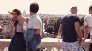 People view the Italian city landscape from the observing platform above the Piazza del Popolo. A happy couple of tourists is making a selfie. Tourists take photos of Rome scenery. Travelling time.