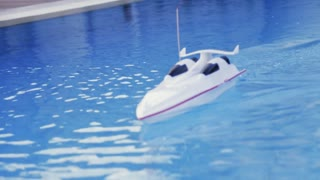 RC boat is sailing in the large pool. Toy boat. No people around. Outside shooting, summertime. Joyful atmosphere, back to childhood. Camera stabilizer shot, close up view.