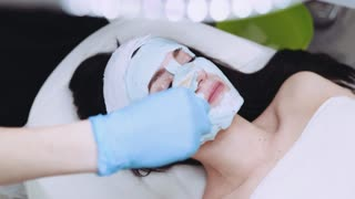 A beautiful female face covered with an organic beauty mask by a professional cosmetologist. Skin care, facial therapy. Natural beauty. Experienced specialist.