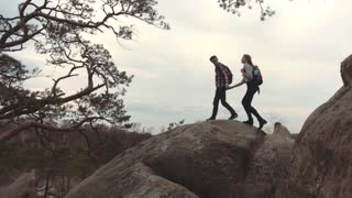 A couple of young lovers with backpacks holding their hands and climbing down the high stoned mountain hill. Tourism, hobby. Happy time together. Admirable nature around.