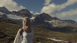 A girl is walking in the Alps mountains, the video is shot under unusual angle. Attractive girl smiles on a background of blue sky.