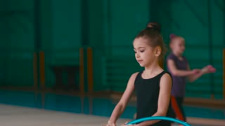 A little cute girl performs gymnastic training, stretching in the sport school, does the ballet pa holding the hula hoop, throws it in the air, catches, jumps, does the vertical split again.