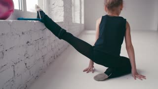 A little girl trains stretching and splits by the window in a specious modern ballet studio. Active lifestyle, healthy life. Being happy, favorite hobby. Leisure time, indoor activity.