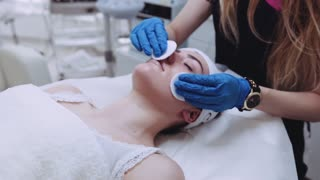A pretty woman with closed eyes, lying on the cosmetologist's table, the dermatologist using cotton sponges to professionally clean the face of the patient. Facial care, being happy, being healthy.