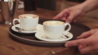 A strong waiters hand carries a brown tray with coffee espresso in two white cups to the customers. Modern cafe. Morning traditions. Cafe settings, wooden furniture on the background.