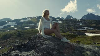 A young girl, with beautiful legs, sits on the mountain peak and observes the scenery.