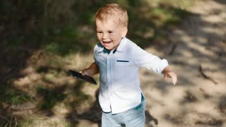 Adorable baby-boy holds the smartphone, posting photos and smiles happily. Modern kids, social networks, little blogger.