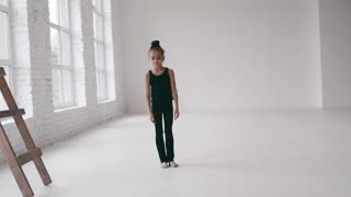 Adorable little ballerina practices the gymnastic stretching, makes a split. Modern kids, talented children. Keeping balance, practicing sport. Leisure time, active hobby. Being happy.