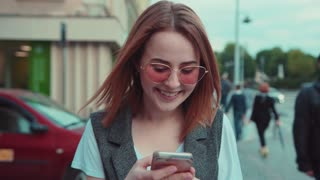 Adorable young red-haired girl wearing stylish sunglasses walks down the city street, uses her phone, dreamily looks around, smiles charmingly. Romantic atmosphere, dreamy mood. Female portrait