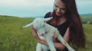 Adorable young woman holding, hugging and kissing cute white goat kid. Nature lover, enjoying life. Slow motion, camera stabilizer shot.