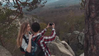 Aerial view of a young adorable people taking selfie on the top of the mountain, smiling, and laughing. Gorgeous scenery on the background. Happy moments. Close up, camera stabilizer shot.