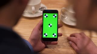 Aerial view of man's hand sliding the greenscreen of the phone, man sitting by the woman in the café. Having fun, technologies. Close up view, slow motion.
