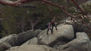 Aerial view of young couple wandering together, climbing down from the top of the rocky mountain, holding their hands. Magnificent nature around. Active lifestyle.
