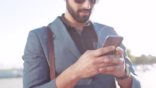Alluring man in a fashionable suit standing by the office entrance, using his phone, replying to the message and joyfully laughing. Positive mood, being happy. Social networks, being online.