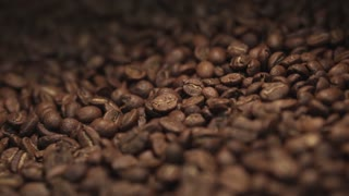Amazing close up view of a big heap of fragrant brown coffee beans in a mixing roasting machine. Coffee making. No people around. International tastes. Inside shooting. Happy coffees day.