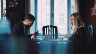 An elegant young couple having a dinner in a luxurious restaurant. Handsome young man in a suit, and elegant blonde woman in luxurious black dress with red lips. First date, romantic atmosphere.