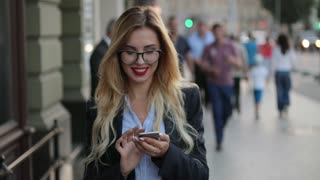 Attractive blonde woman with red lipstick, in a business suit walking down the crowded central street, passing by the street musician and using her phone, reacting happily to the message.