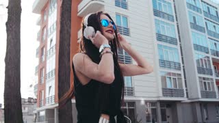Attractive brunette girl in a black blouse enjoying the music in a bright sunshine, dances and sings along emotionally, gestures actively. Stylish look. Sunny day, spring time. Relaxation time.