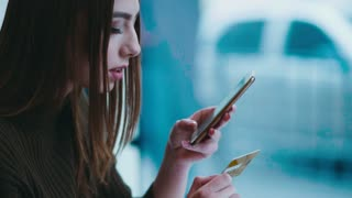 Attractive brunette woman using her phone and credit card for online shopping. Modern technologies, contemporary people. Having fun, online activities.