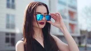 Attractive brunette woman with passionate red lips, and nose piercing looks to the camera and takes off the sunglasses. Natural beauty, female portrait, seductive look.