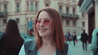 Attractive happy woman walks down the crowded city street and uses her phone, smiles happily, strokes her hair around. Moments of joy, pleased, excited. Good mood. Female portrait