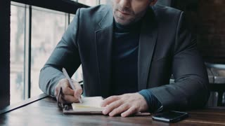 Attractive man in a formal black suit putting a signature on the documents, then looks right towards the camera. Office interior on the background. Successful lifestyle. Male portrait.