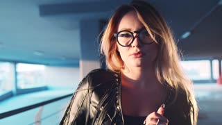 Attractive sexy blonde girl walks down the parking, and looks seductively right towards the camera, emotionally corrects her leather jacket and eyeglasses. Hot nerdy girl. Natural beauty.