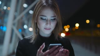 Attractive smiling girl in the dark clothes is on the evening street. She is near the business center. The girl is concentrated on her smartphone. She is texting with someone in the telephone.