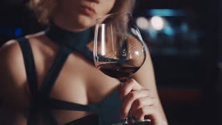 Attractive woman in a sexy dress playing with a wineglass, being sad, then looks at bearded man in a black suit and gives a charming smile, he talks to her, she looks pleased and gladly talks back.