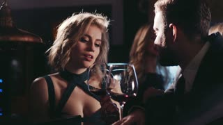 Attractive young blonde woman in a sexy dress playing with a wineglass, talking to a bearded man in a black suit, cheering and flirting to each other. Modern relationships, first date.