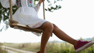 Attractive young girl in an elegant white dress and snickers enjoys summertime, sways on a wooden swing seat in the summer garden. Having fun, vacation, happy memories