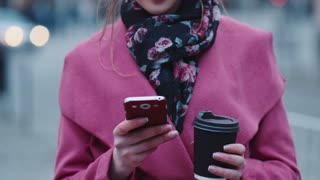 Attractive young girl with casual haircut holding a cup of hot coffee and using her cell phone for texting, then looks right in the camera and smiles happily. Busy lifestyle, modern girls.