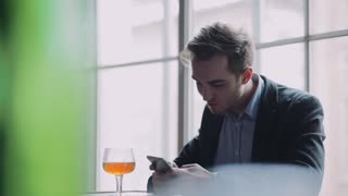 Attractive young man sits alone in the bar, uses his phone, takes photo, surfs the internet, takes a sip of the beer and is surprised with its taste. Having fun, social networks. Alcohol party.