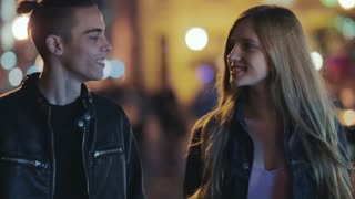 Attractive young people having a romantic date, walking down the city at night, hug and kiss each other. Happy together, strong feeling. Camera stabilizer shot