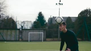 Attractive young sportsmen heading a soccer ball to each other. Professional sport, training. Sportive lifestyle, being happy. Having fun, football tricks.