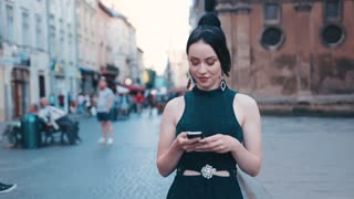 Attractive young woman in casual black dress and with beautiful ponytail walks down the historical city center, and uses her phone, looks around, gladly texts back. Playful mood, modern lifestyle.