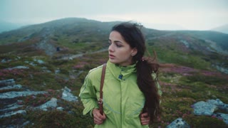 Attractive young woman with a backpack walks alone in the rocky mountains. Active lifestyle, green tourism, joy of life. Pure nature. Slow motion, camera stabilizer shot, female portrait