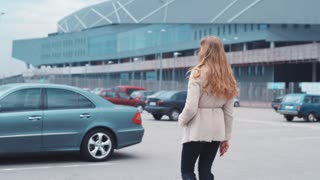 Back view of a beautiful young European girl with a long hair, in a warm coat using the remote control to unlock the alarm system of a luxurious car, and sitting in.