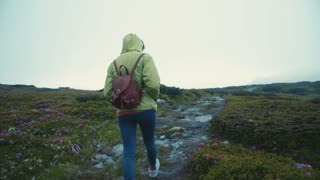 Back view of a fit young female hiker with a backpack walking down the stoned mountain path. Extreme, active lifestyle. Indie look, hipster. Foggy weather, strong wind. Slow motion