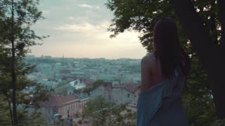 Back view of a long haired brunette woman in trendy stripped outfit observing the old cityscape at the sunset, stroking hair. Dreamy mood, romantic atmosphere, journey Active lifestyle Female portrait