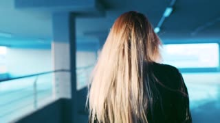 Back view of blonde long-haired young girl walking down the parking, turning to camera and playfully smiling in a bright sunshine. Modern nerdy style, hipster. Natural beauty, cheerful mood.