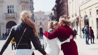 Back view of three fit woman walking in the city center, then turning to camera and laughing happily and playful. Casual wear. Women in the city. Real friendship, trust. Windy weather.