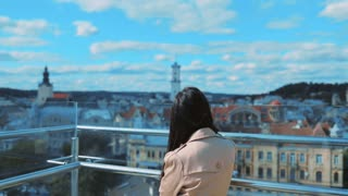 Back view of young woman standing on top of the tower observation deck enjoying the view of old city. Relaxation, tourist, having fun