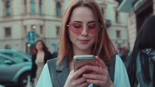 Beautiful cheerful young woman wearing trendy rose sunglasses walks down the crowded street, uses phone, smiles happily, touches her hair Fashion icon, flirting, social networks. Browsing the internet