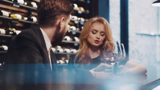 Beautiful couple having a conversation with glasses of wine by the bar, smiling, flirting. Handsome young man in a suit, and elegant blonde woman in luxurious black dress with red lips.