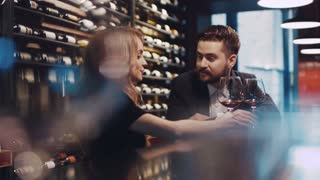 Beautiful couple of a young people sitting by the bar, having a glass of red wine and talking actively to each other. Handsome young man and elegant woman in luxurious black dress with red lips.