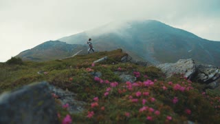 Beautiful girl in a stylish outfit wandering in the moist mountain hills and admiring the landscape. Pure nature, adventure, relaxation, being alone. Indie look, hipster. Slow motion